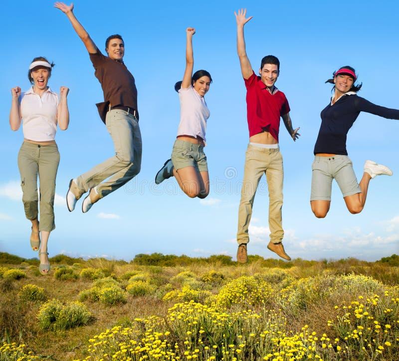 Grupo feliz de salto dos jovens em flores amarelas fotos de stock royalty free