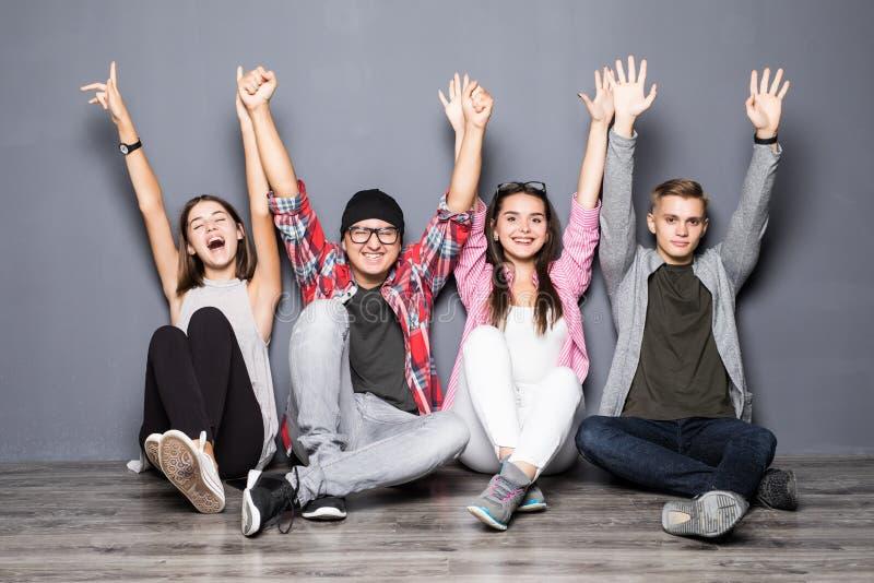 Grupo feliz de sonrisa de los amigos y de feliz aumentada de las manos salidos fotos de archivo