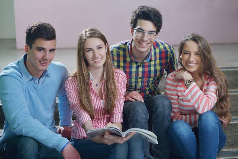 Grupo feliz dos adolescentes na escola imagens de stock