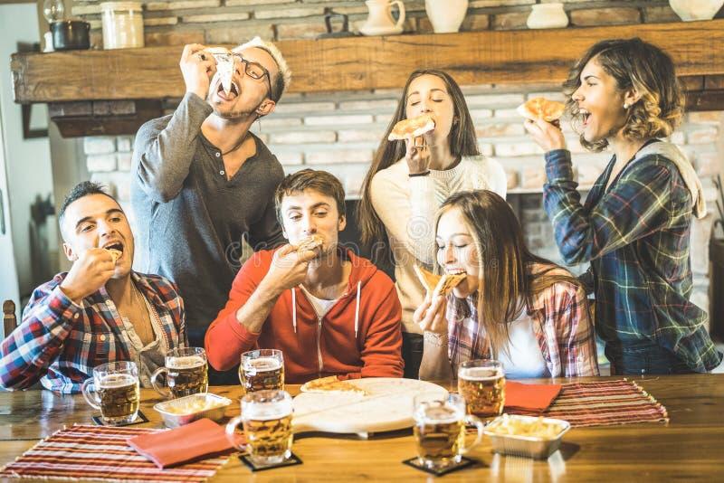 Grupo feliz dos amigos que come a pizza na casa do restaurante do chalé imagens de stock royalty free