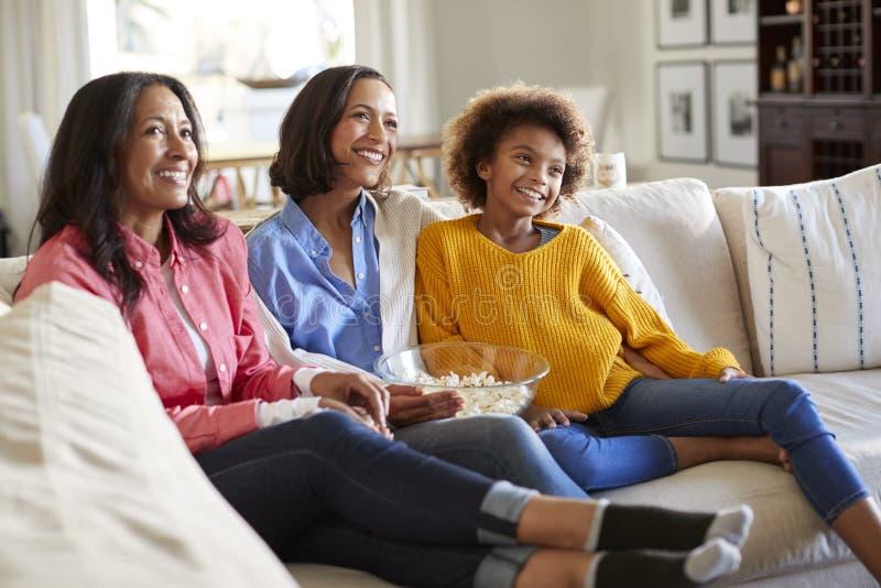 Grupo femenino de la familia de la familia de tres generaciones que pasa el tiempo junto que se sienta en el sofá que ve la TV en fotografía de archivo libre de regalías