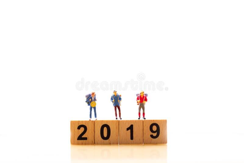 Grupo figuras miniatura y de la palabra 2019 del viajero de las mini del bloque de madera en fondo blanco aislado imagen de archivo