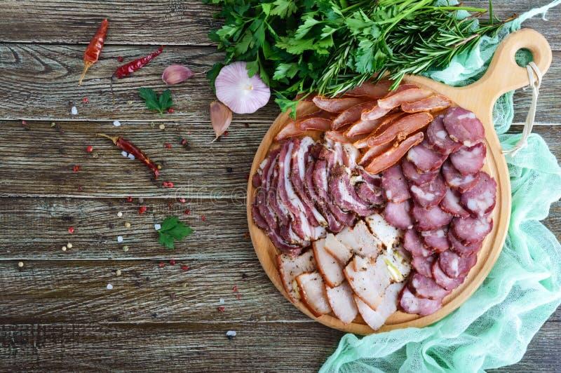 Grupo grande da carne A salsicha fumado caseiro da carne de porco-carne, bacon salgado, basturma desbastou fatias em uma placa de imagens de stock