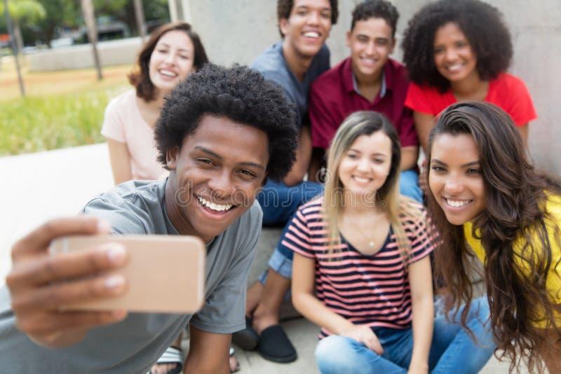 Grupo grande de adultos jovenes internacionales que toman el selfie con pho fotografía de archivo libre de regalías