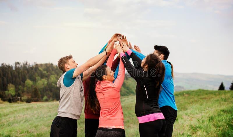 Grupo grande de ajuste y gente activa que descansa después de hacer ejercicio en naturaleza foto de archivo