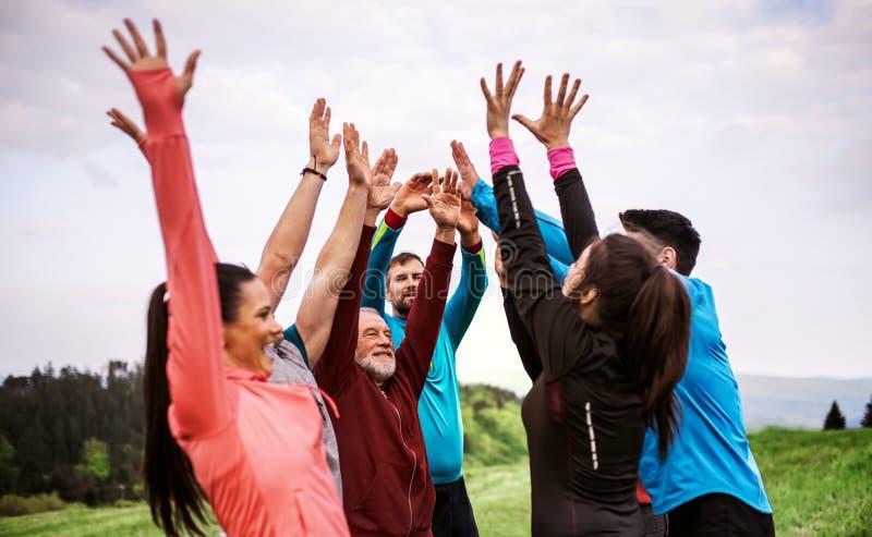 Grupo grande de ajuste y gente activa que descansa después de hacer ejercicio en naturaleza fotografía de archivo libre de regalías