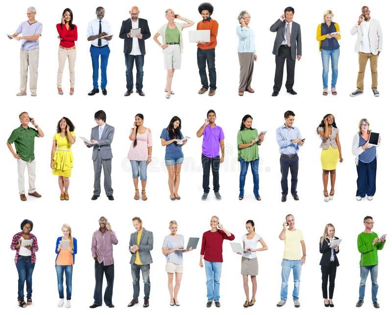 Grupo grande de gente diversa que usa los dispositivos de Digitaces imagen de archivo