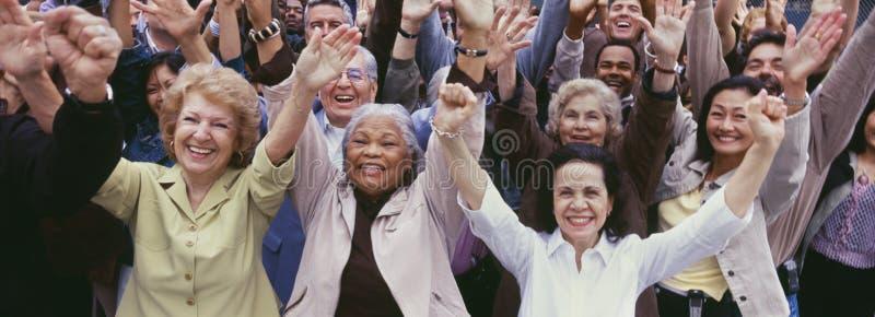 Grupo grande de gente multi-étnica que anima con los brazos aumentados imágenes de archivo libres de regalías