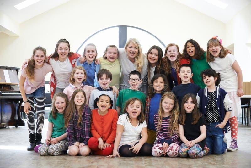 Grupo grande de niños con el Tog de Enjoying Drama Workshop del profesor fotos de archivo