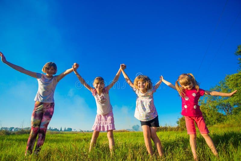 Grupo grande de niños que corren en campo del verano foto de archivo