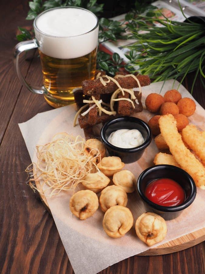 Grupo grande de petiscos para a cerveja inclui bolas fritadas do queijo, queijo da trança, bolinhas de massa fritadas imagens de stock