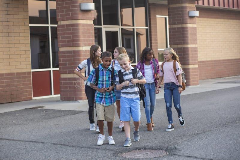 Grupo grande, diverso de niños que salen de la escuela al final del día Amigos de la escuela que caminan junto y que hablan junto foto de archivo