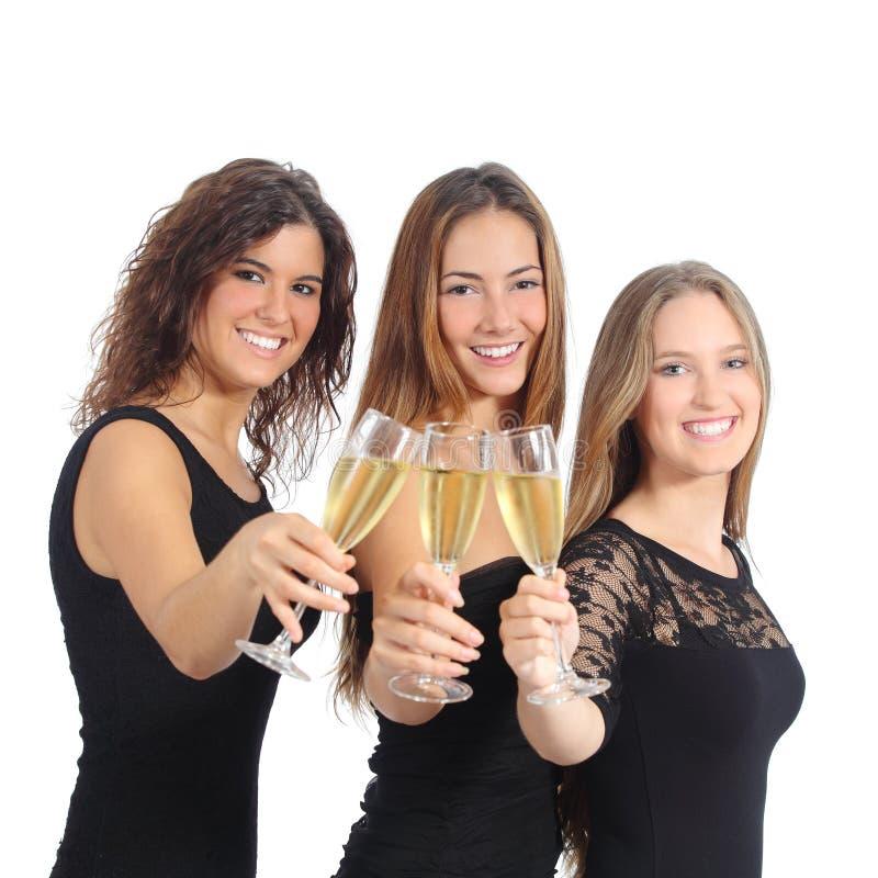 Grupo hermoso de tres mujeres que tuestan con champán imagenes de archivo
