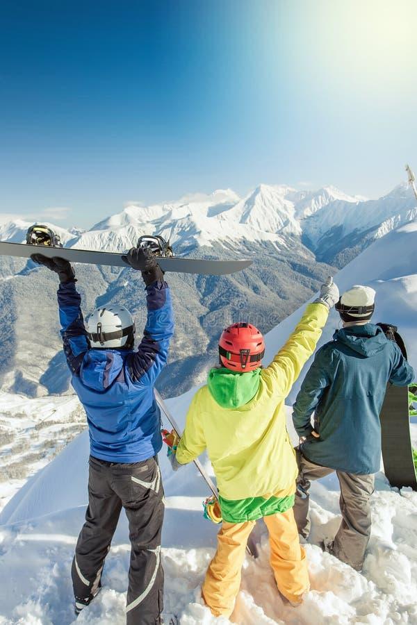 Grupo inspirado de snowboarders na cimeira imagens de stock