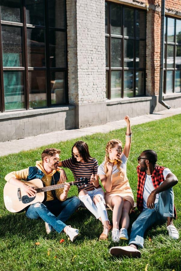 grupo inter-racial de amigos com a guitarra acústica que descansa na grama verde fotos de stock royalty free