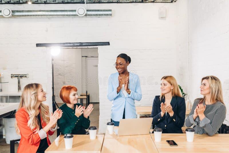 Grupo internacional de mujeres felices que celebran éxito en la reunión del equipo foto de archivo libre de regalías