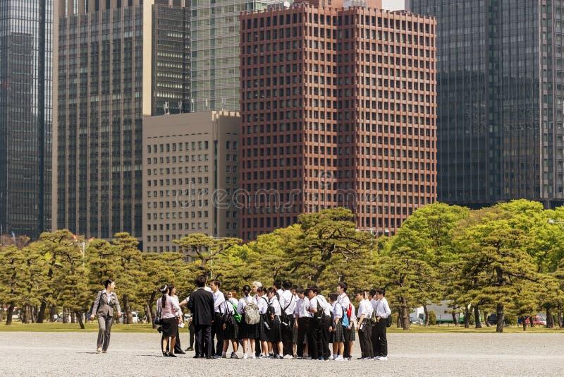 Grupo japonés de la escuela que visita el palacio imperial en Tokio con los rascacielos de Chiyoda, Japón en el fondo imagenes de archivo