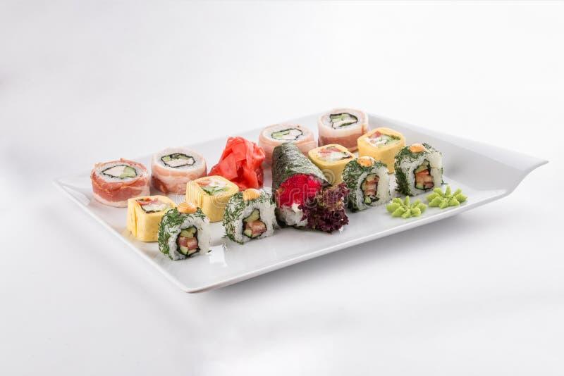 Grupo japonês da placa ou da bandeja do rolo do maki do sushi do restaurante do alimento isolado no fundo branco fotografia de stock
