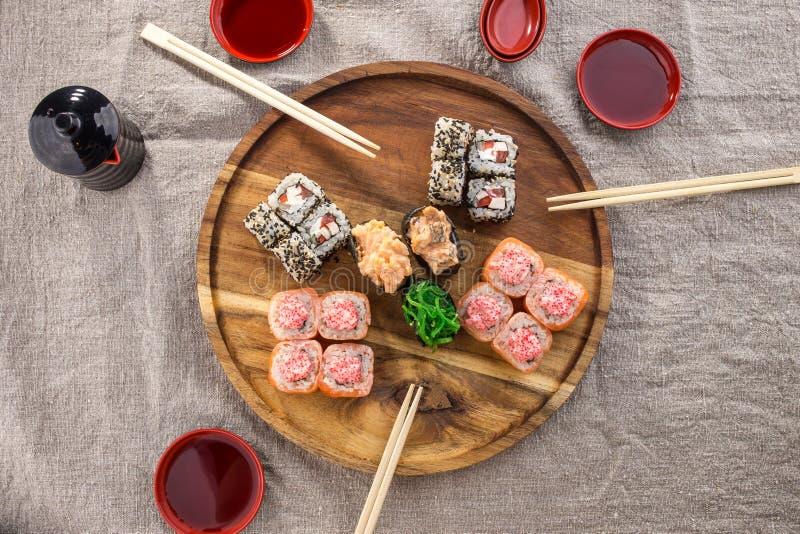 Grupo japonês do rolo do maki do sushi do restaurante do alimento na placa redonda de madeira com os hashis no fundo cinzento da  imagens de stock royalty free