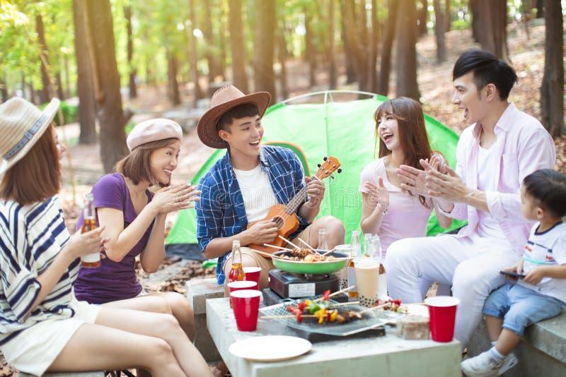Grupo joven asiático que disfruta del partido y de acampar de la comida campestre foto de archivo