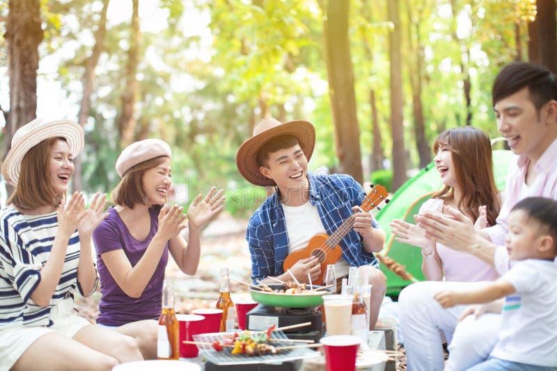 Grupo joven asi?tico que disfruta del partido y de acampar de la comida campestre fotografía de archivo libre de regalías