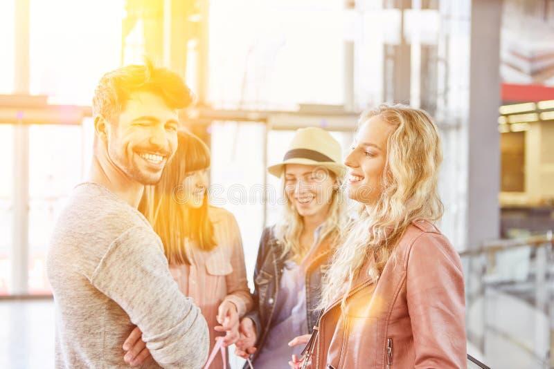 Grupo joven de amigos en una alameda de compras foto de archivo
