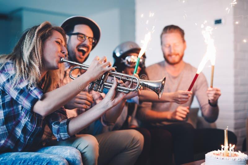 Grupo joven de amigos felices que celebran cumpleaños imagenes de archivo