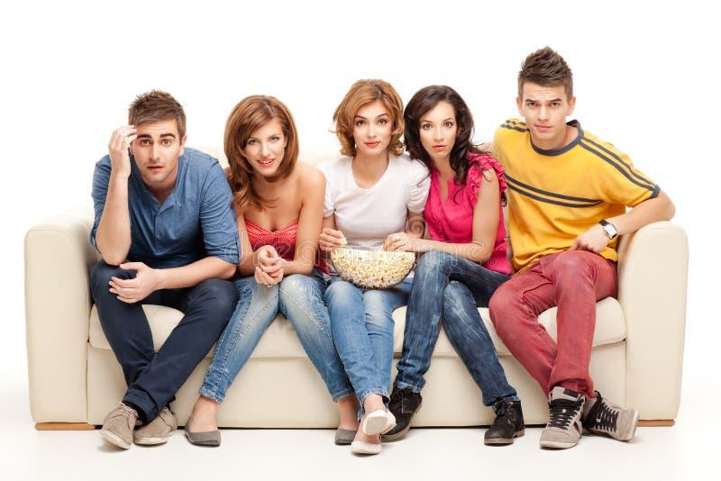 Grupo joven de amigos que miran película que pregunta fotos de archivo libres de regalías