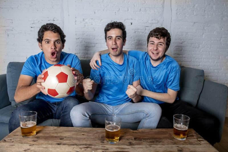 Grupo joven de hombres felices y emocionados que miran un partido de fútbol en el sofá foto de archivo libre de regalías