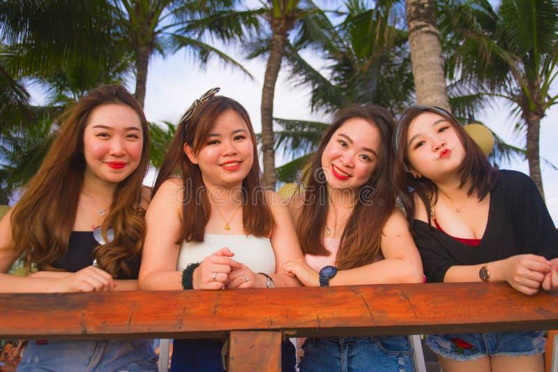 Grupo joven de muchachas chinas asiáticas felices y hermosas que tienen días de fiesta junto que cuelgan hacia fuera el goce en e fotografía de archivo