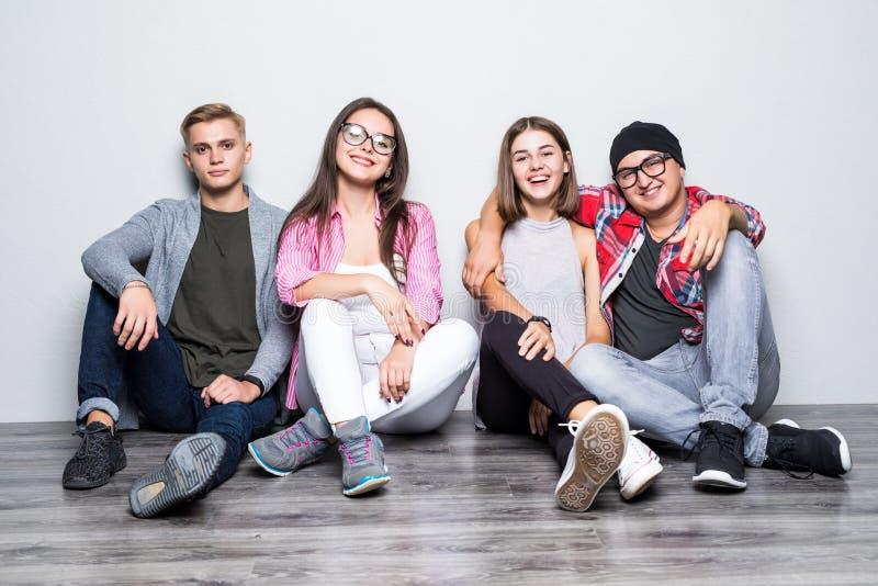 Grupo joven de teengers de los estudiantes de los amigos que se sientan en piso foto de archivo libre de regalías