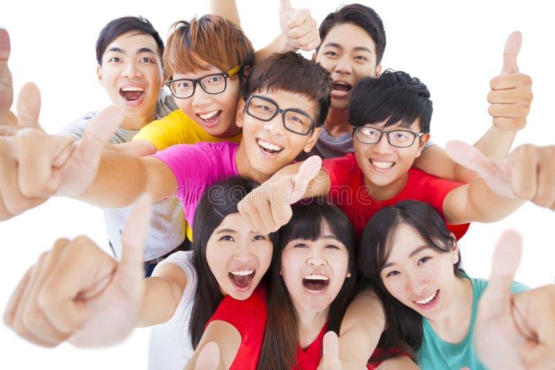 Grupo joven feliz con los pulgares para arriba imagen de archivo
