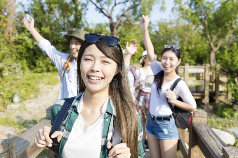 Grupo joven feliz que camina junto a través del bosque imagen de archivo