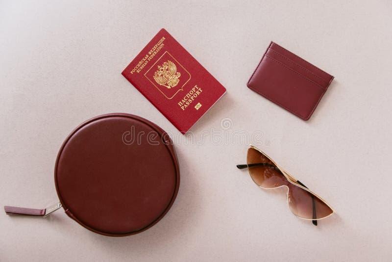 Grupo mínimo fêmea do curso Passaporte marrom, possuidor de cartão e carteira com um saco e vidros em um fundo bege pastel foto de stock