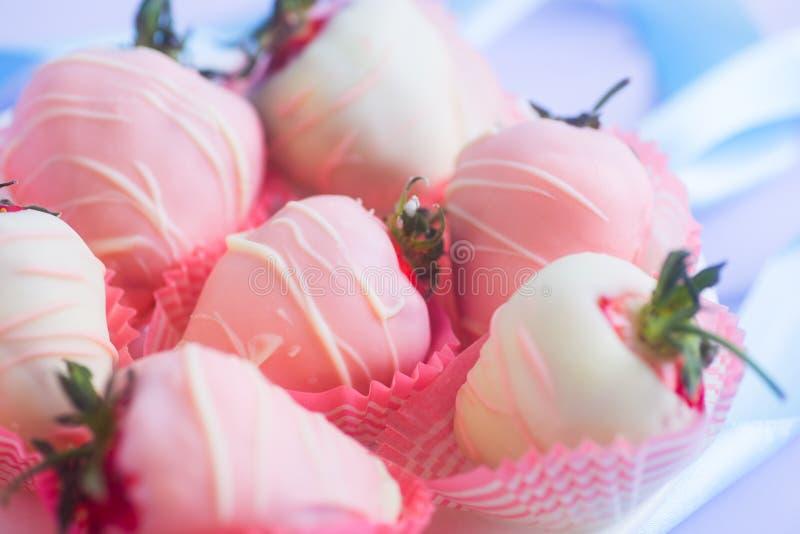 Grupo macio da morango do close up vitrificado no chocolate cor-de-rosa e branco decorado com tiras no fundo lilás imagem de stock