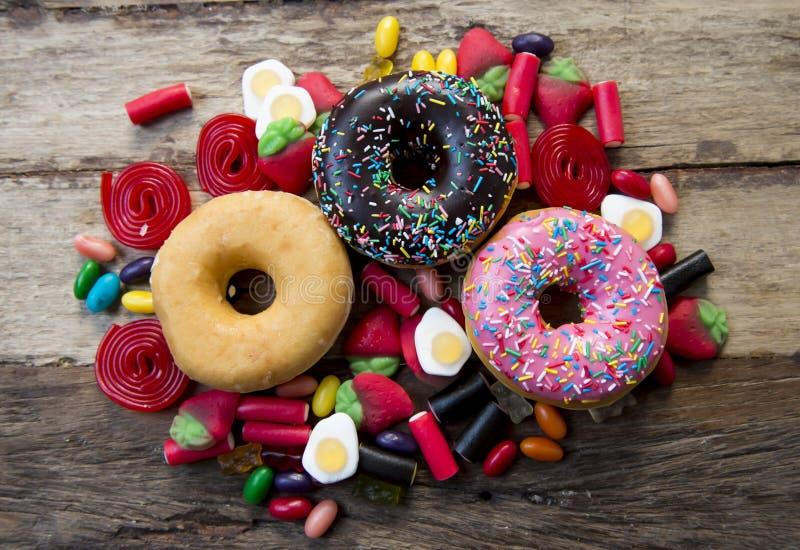 Grupo malsano pero delicioso de tortas dulces del buñuelo del azúcar y porciones de caramelos gomosos en la tabla de madera del v imagen de archivo libre de regalías