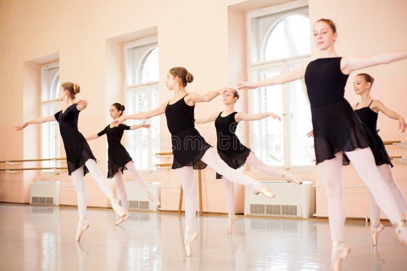 Grupo medio de adolescentes en los vestidos negros que practican movimientos del ballet en un estudio grande de la danza imágenes de archivo libres de regalías