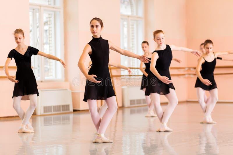 Grupo medio de adolescentes que practican movimientos del ballet imagen de archivo