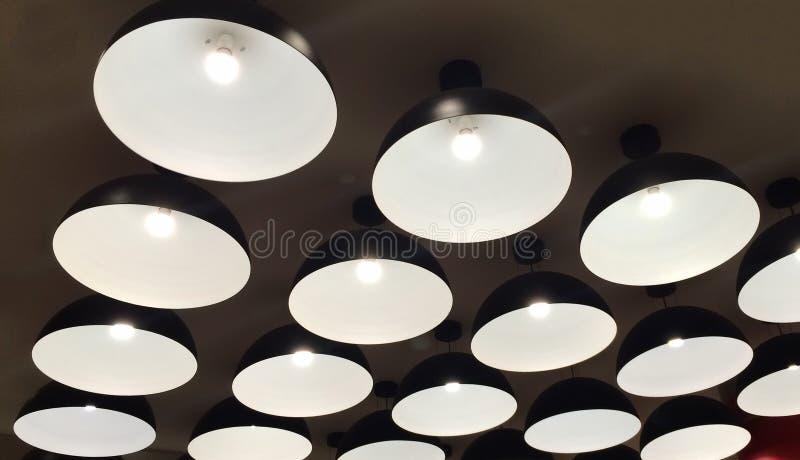 Grupo metal preto moderno de lâmpadas iluminadas que penduram no teto fotografia de stock royalty free