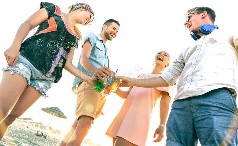 Grupo millenial feliz de los amigos que se divierte en el partido de la playa que bebe los cócteles de lujo en la puesta del sol  fotos de archivo libres de regalías