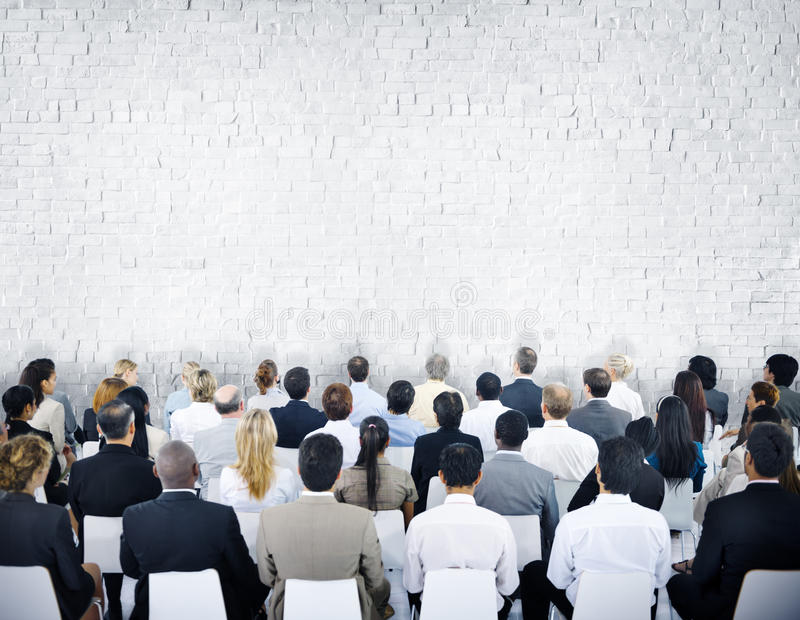 Grupo multiétnico de audiencias con la pared de ladrillo imagenes de archivo