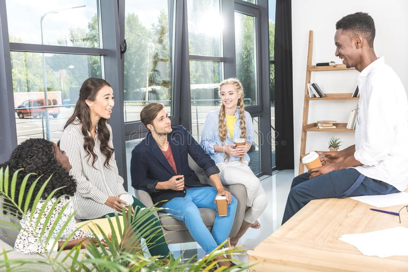 grupo multiétnico de compañeros de trabajo del negocio que tienen conversación durante descanso para tomar café foto de archivo libre de regalías