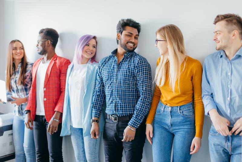 Grupo multiétnico de gente joven en ropa de sport aislada sobre fondo gris imagen de archivo