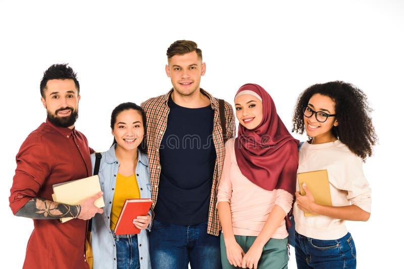 grupo multiétnico de gente joven que se coloca con los libros aislados fotografía de archivo