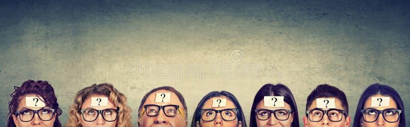 Grupo multiétnico de gente de pensamiento en vidrios con el signo de interrogación que mira para arriba foto de archivo
