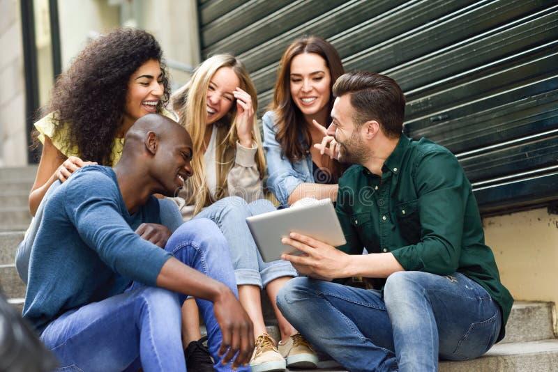 Grupo multiétnico de jovens que olham para um tablet fotografia de stock
