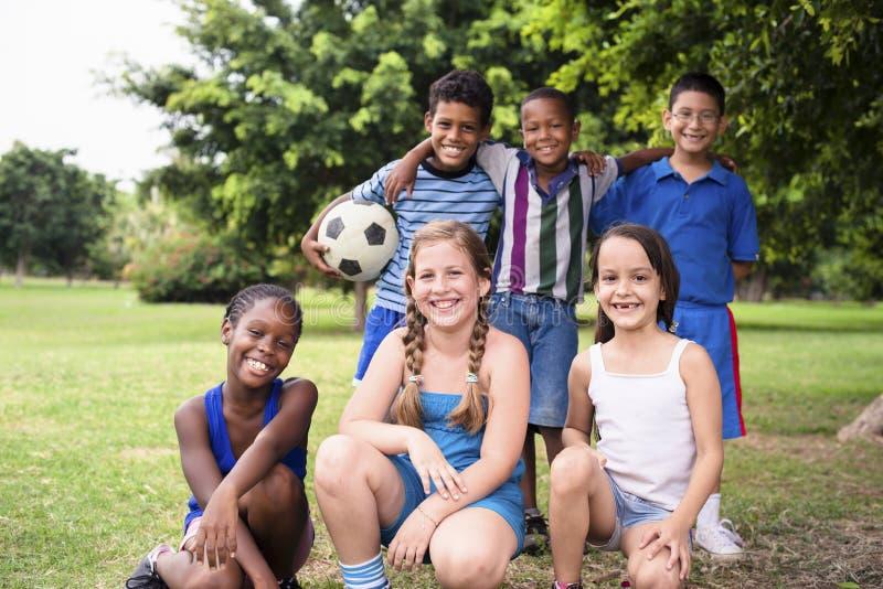 Grupo multiétnico de niños con el balón de fútbol fotografía de archivo