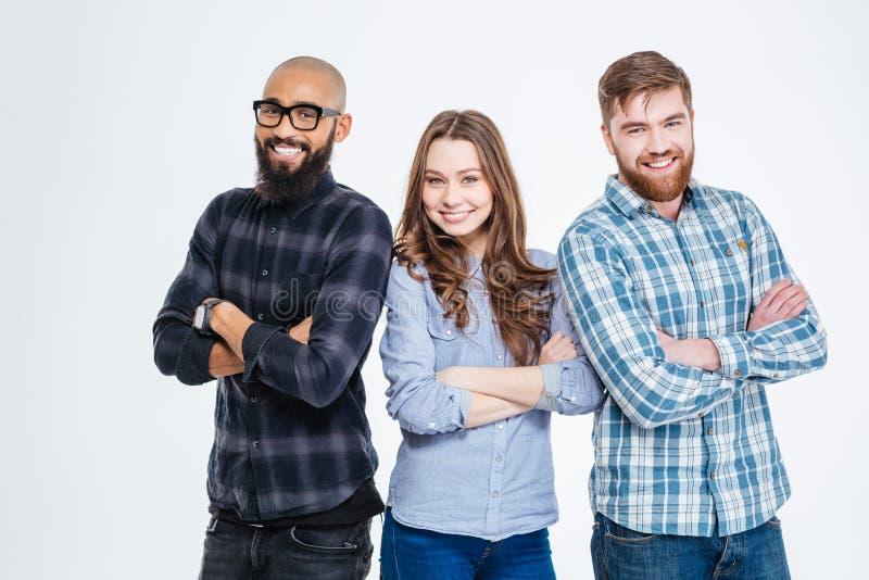 Grupo multiétnico de tres estudiantes sonrientes confiados imagenes de archivo