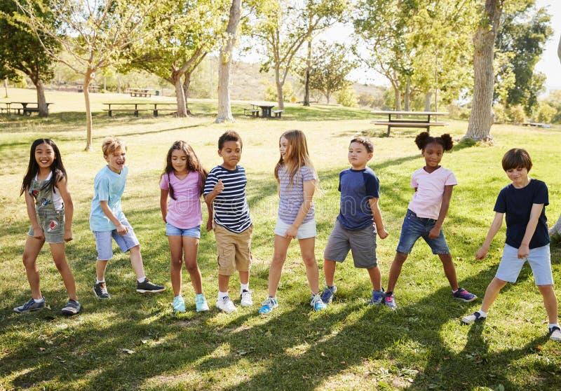 grupo Multi-étnico de alumnos que juegan en parque fotos de archivo