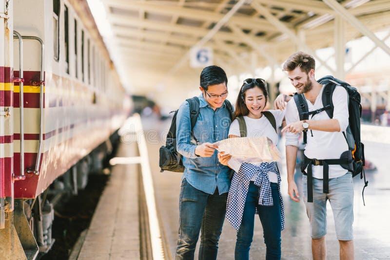 Grupo multi-étnico de amigos, de viajantes da trouxa, ou de estudantes universitário que usam a navegação local do mapa junto no  fotos de stock royalty free